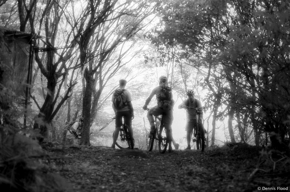 Mountain bikers rest on the backyard trail before continuing downhill the photo was taken on grainy infrared black and white film